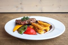 Pork meal with potato slices and a tomato. In a big white plate on a wooden surface stock photography