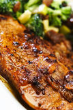Pork Meal with Salad. A well fried pork steak (with onions) with garniture of vegetables - closeup image with a very shallow DOF Royalty Free Stock Image