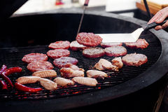 Pork meat and chicken cutlets with pepper grilling for burgers. Chef working with spatula. catering in food court at mall concept. space for text stock images