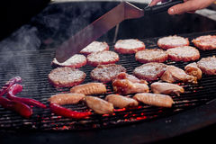Pork meat and chicken cutlets with pepper grilling for burgers. Chef working with spatula. catering in food court at mall concept. space for text royalty free stock photos