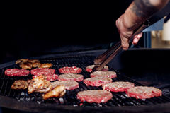 Pork meat and chicken cutlets with pepper grilling for burgers. Chef working with tongs. catering in food court at mall concept. space for text. open kitchen stock image