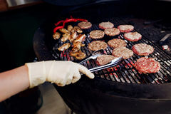 Pork meat and chicken cutlets with pepper grilling for burgers. Chef working with tongs in gloves. catering in food court at mall concept. space for text stock image