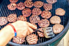 Pork meat and chicken grilling for burgers with flames and smoke. Catering in food court at mall. Selective focus, close up. Fast food cafe cuisine. open royalty free stock photos