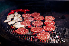 Pork meat and chicken grilling for burgers with flames and smoke. Catering in food court at mall. space for text. open kitchen royalty free stock photos