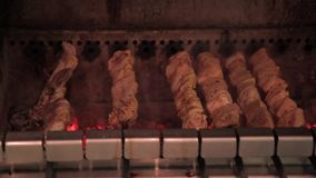 Pork meat is cooked on skewers in oven indoors. stock footage
