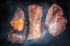 Pork meat hanging on hooks in smoke. Preparing smoked ham. Stock Images