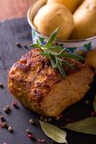 Pork meat with rosemary branch on slate stone. Vertical photo of baked piece of pork meat with green rosemary herb on the top. Color pepper, bay leaf, onion Stock Images