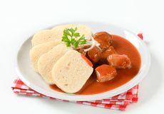 Pork meat in tomato sauce with dumplings Royalty Free Stock Image