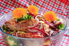 Pork meat with vegetables and dandelions in glass bowl Royalty Free Stock Image