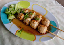 Pork meatballs on a plate topped with sauce and a cucumber. Royalty Free Stock Photo