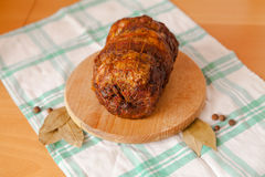 Pork meatloaf on wooden cutting board. On white and green towel on light wooden background with bay leaves and black pepper Stock Image