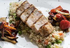 Pork medallions with grilled vegetables and vegetable couscous. Excellent food stock images