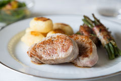 Pork medallions with potatoes and beans. Wrapped in bacon royalty free stock photo