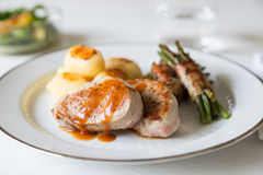Pork medallions with potatoes and beans Stock Images
