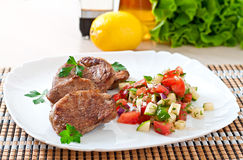 Pork medallions with salsa. On plate royalty free stock photo