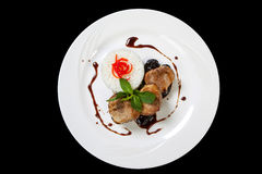 Pork medallions steak with prunes sauce on a white plate stock image