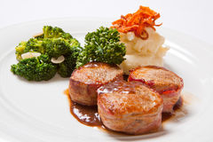 Pork medallions wrapped in bacon, with potatoes and broccoli.  Royalty Free Stock Photography