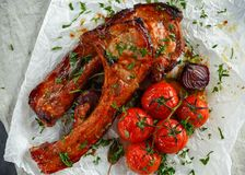 Pork middle chop roast with sweet and sour souce, baked tomatoes and red onion.  royalty free stock photo