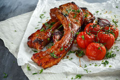 Pork middle chop roast with sweet and sour souce, baked tomatoes and red onion.  stock photo