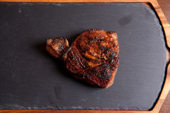 Pork neck chop on slate Royalty Free Stock Images