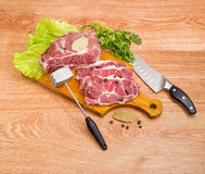 Pork neck on cutting board, meat tenderizer and kitchen knife. Partly sliced uncooked pork neck, lettuce leaves and spices on wooden cutting board, bunch of the Royalty Free Stock Photo