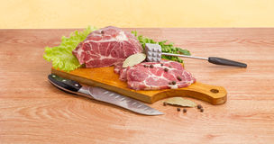 Pork neck on cutting board, meat tenderizer and kitchen knife. Partly sliced uncooked pork neck, lettuce leaves and spices on wooden cutting board, bunch of the Stock Photography
