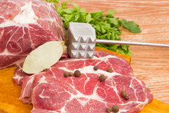 Pork neck on cutting board, spices, meat tenderizer closeup Stock Photo