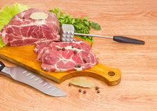 Pork neck on cutting board, spices, meat tenderizer and knife Royalty Free Stock Images