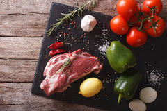 Pork neck raw and ingredients on a slate board. horizontal top v Royalty Free Stock Images