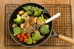 Pork neck steak in a cast iron pan with vegetables Royalty Free Stock Photo