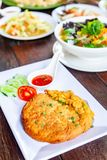 Pork Omelet on White Plate with Som Tam and Many Food on Wood Ta. Pork Omelet and Sauce on White Plate with Som Tam and Many Food on Wood Table Royalty Free Stock Image
