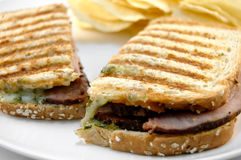 Pork Panini. Grilled sandwich with potato chips on a white plate Royalty Free Stock Images