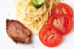 Pork with pasta and tomatoes Royalty Free Stock Photography