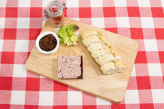Pork pate. Ardennes pate on a wooden board with pickle, tomatoes, lettuce and slices of baguette Royalty Free Stock Photography