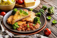 Pork Piccata with tomato sauce and steamed broccoli and boiled potatoes. Piccata - fried pork cutlets stuffed with smoked ham slices coated in cheese and eggs stock photo