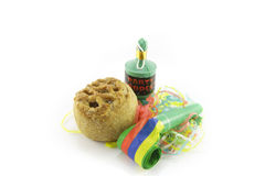 Pork Pie with Blower and Party Popper. Small tasty pork pie with party blower and party popper with streamers on a reflective white background Stock Photo