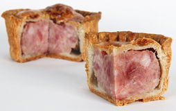 Pork Pie Isolated. Small pork pie cut as a quarter with blurred three quarter pork pies in background Royalty Free Stock Images