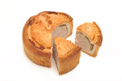 Pork Pie and slice. Photograph of a pork pie shot in studio and isolated on a white background, with two slices Royalty Free Stock Photography