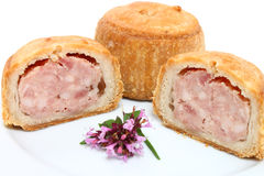 Pork Pies. Pork pie and two half slices on a white plate Stock Photo
