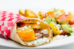 Pork pita wrap. With side salad and potatoes, fresh heirloom tomatoes and feta Royalty Free Stock Photos