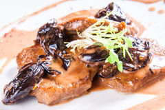 Pork with prunes. On white plate stock photography