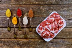 Pork raw meat and ingredients with different spices on a old wooden table. Pork raw meat and ingredients spoons with different spices on a old wooden table Stock Photos