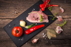 Pork raw meat. On a stone plaque located on old wooden table Stock Image