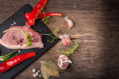 Pork raw meat. On a stone plaque located on old wooden table Stock Photo