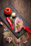 Pork raw meat. On a stone plaque located on old wooden table Royalty Free Stock Photo