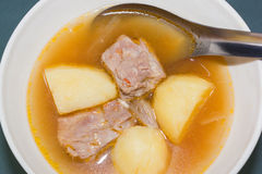 Pork rib soup. In the white bowl with tomato, onion and potato stock photos