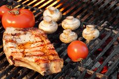 Pork Rib Steak, Tomato And Mushrooms On Hot BBQ Grill Royalty Free Stock Photo
