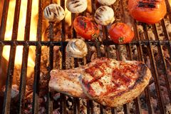 Pork Rib Steak, Tomato And Mushrooms On Hot BBQ Grill Royalty Free Stock Image