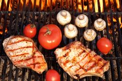 Pork Rib Steaks, Tomato And Mushrooms On Hot BBQ Grill Stock Images