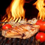 Pork Rib Steaks, Tomato And Mushrooms On Hot BBQ Grill Royalty Free Stock Photography
